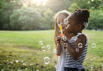 Summer Program: Two girls blowing bubbles