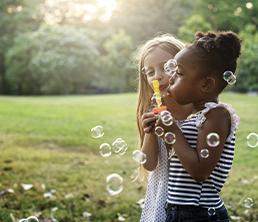 Summer Program: Two girls blowing bubbles