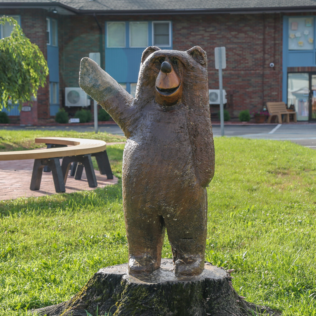 Wooden bear waving in front of the building