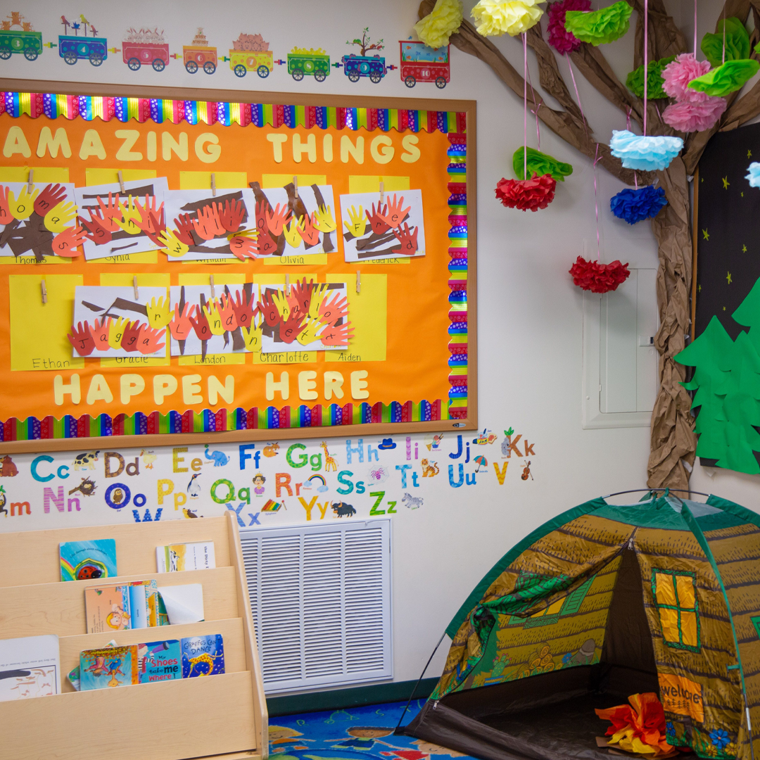 Inside a preschool classroom with a tent and Amazing Things Happen Here bulletin board
