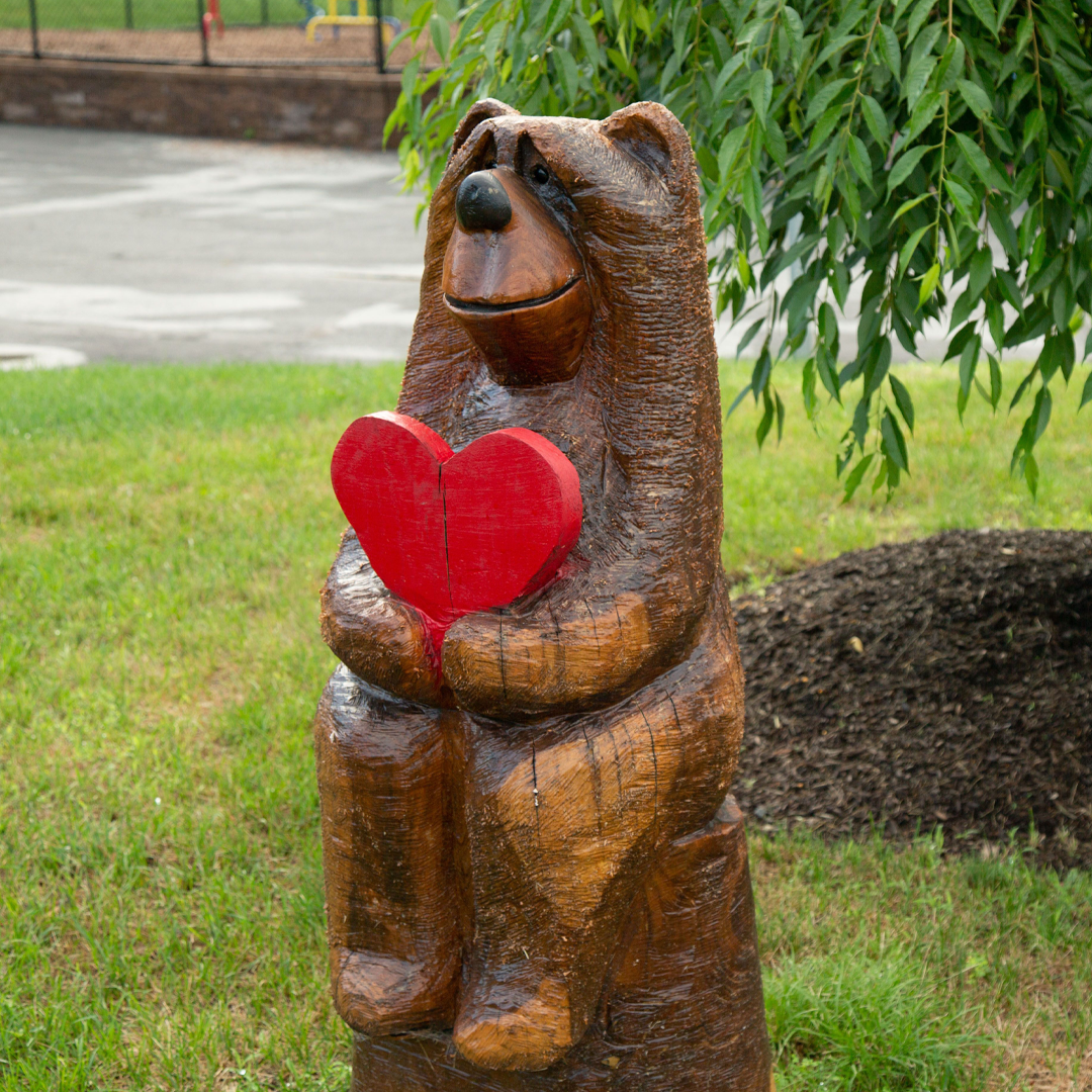 Wooden bear holding a heart in front of the remembrance tree