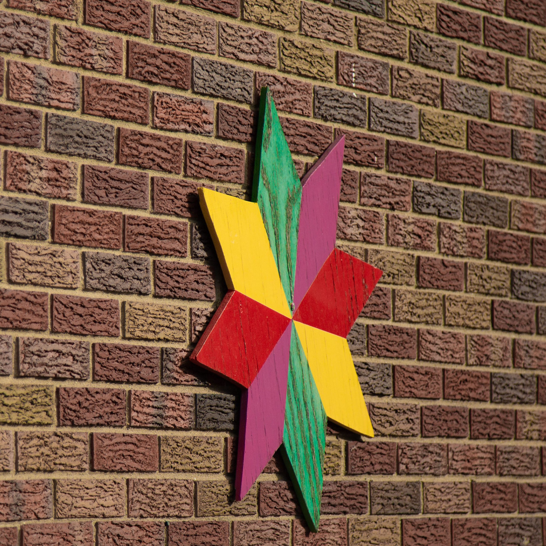 Wooden star that is yellow, red, pink and green